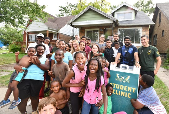 Wayne State University medical students and children from Auntie Na's House gather in front of a medical clinic they are setting up to provide health services for the neighborhood in Detroit.