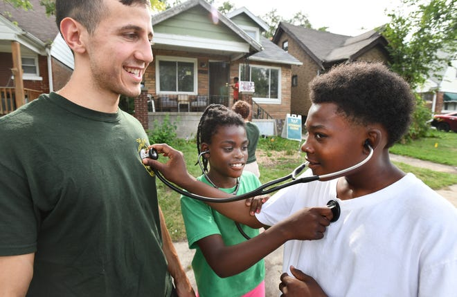 WSU medical student Ali Dakka lets Justin Brown use his stethoscope, listening for a heartbeat, as Jiya Brown, 10,  listens for Justin's heartbeat.  Wayne State University medical students setting up a medical clinic as part of Auntie Na's House, providing much needed medical services for the Detroit neighborhood.