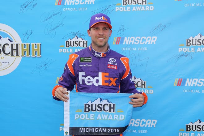 Denny Hamlin, driver of the No. 11 FedEx Office Toyota, poses with the pole award after qualifying for the Monster Energy NASCAR Cup Series Consumers Energy 400 at Michigan International Speedway on Friday.
