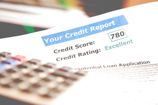 Know your credit score!  Credit report documents including score and rating along with a calculator and residential loan application on desk.  Other books, documents in background.