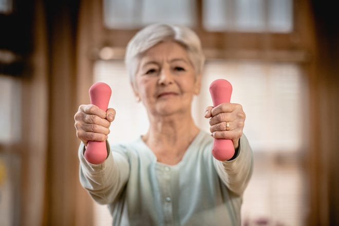 A senior woman with gray hair exercising in the living room. She is holding two small pink dumbbells in front of her body.