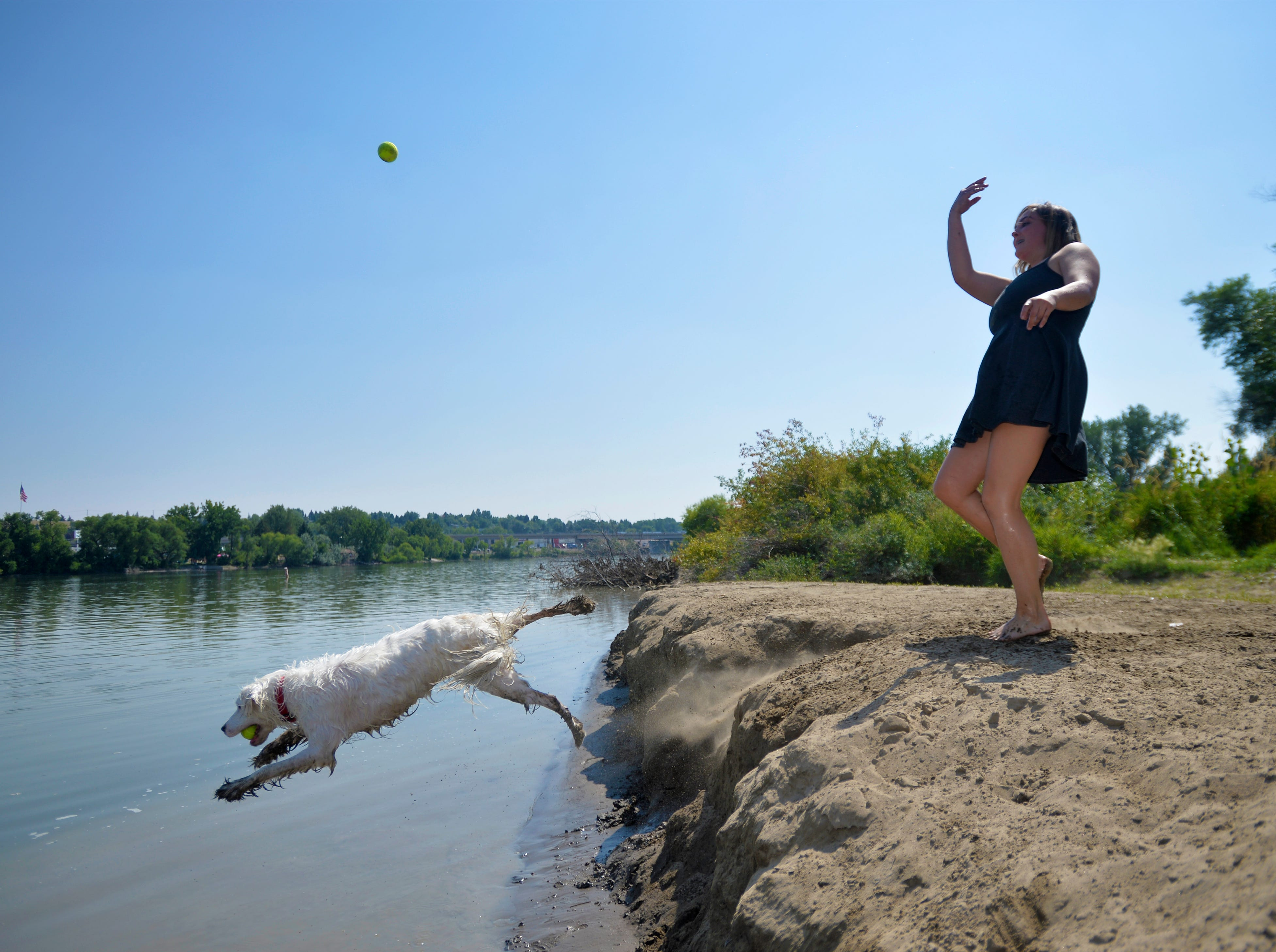 Lacey Mans throws another tennis ball for Max as they try to stay cool in Thursday's heat wave.