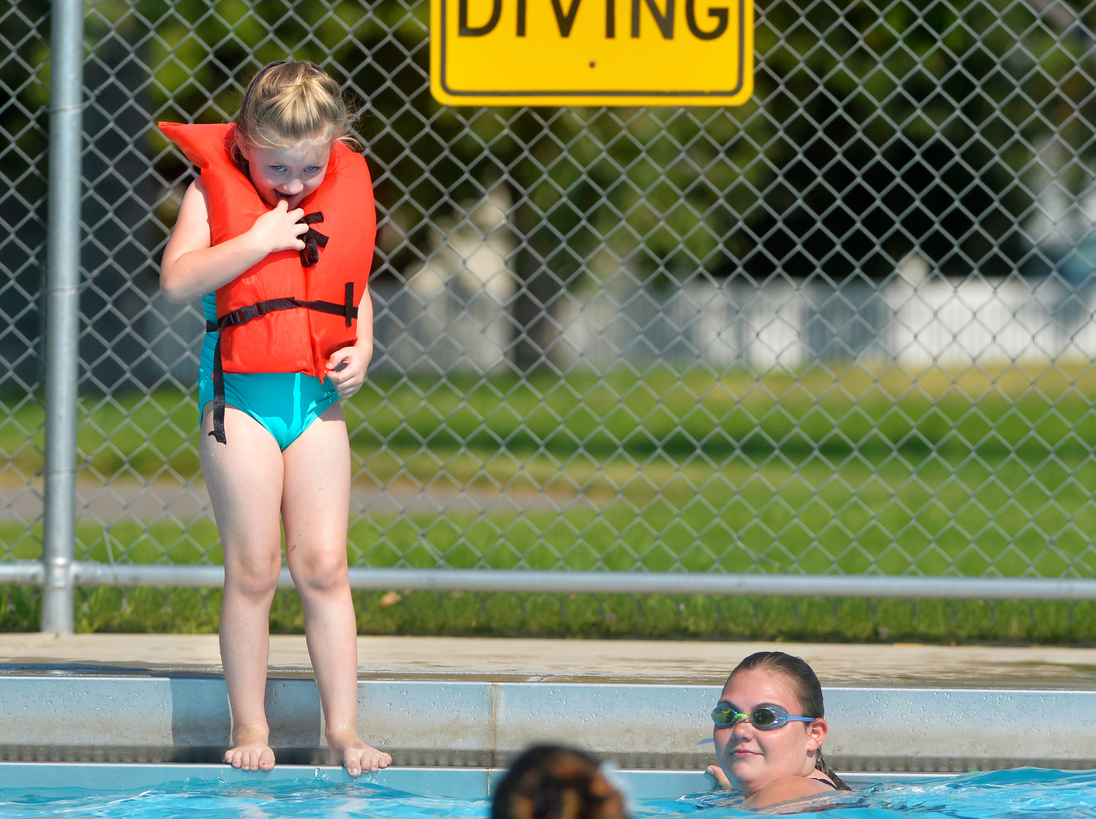 Ivy Bauer, age 5, inches closer to jumping in with some encouragement from her family on Thursday at the Water Tower Pool.