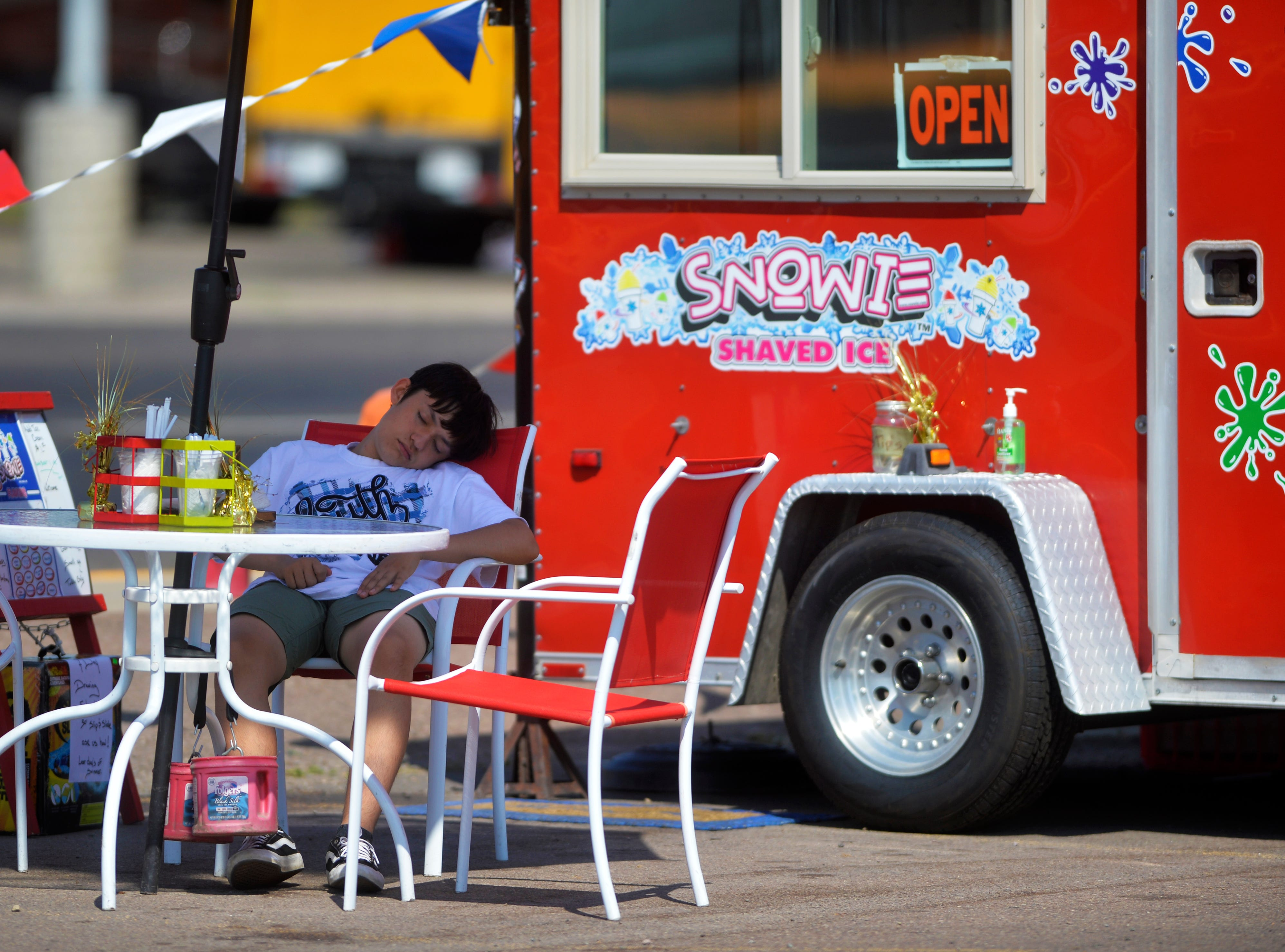 Colt Lalonde catches a cat-nap in the 100 degree weather as he waits for his next customer at the Snowie Shaved Ice stand, Thursday.