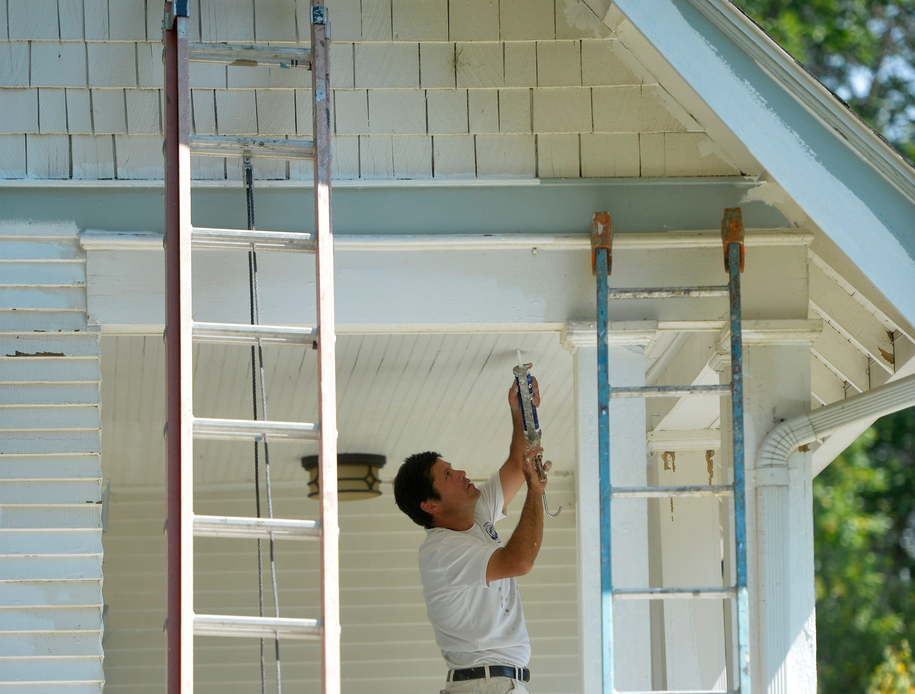 Warren Chamakoon of C's Painting preps a house for painting on Thursday afternoon as the temperature approaches 100 degrees.