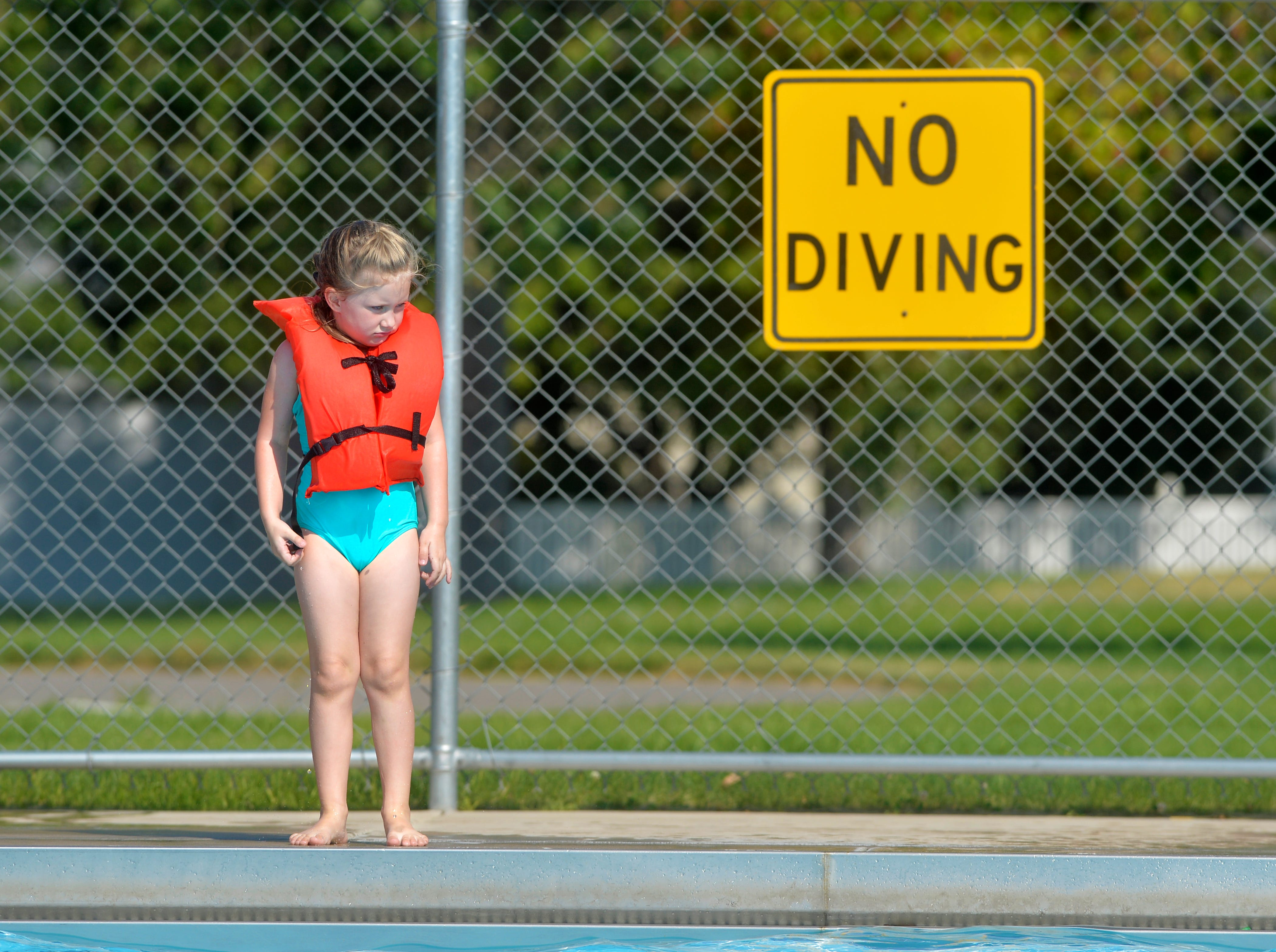 Ivy Bauer, age 5, thinks about jumping in the deep end of the Water Tower Pool on Thursday afternoon.
