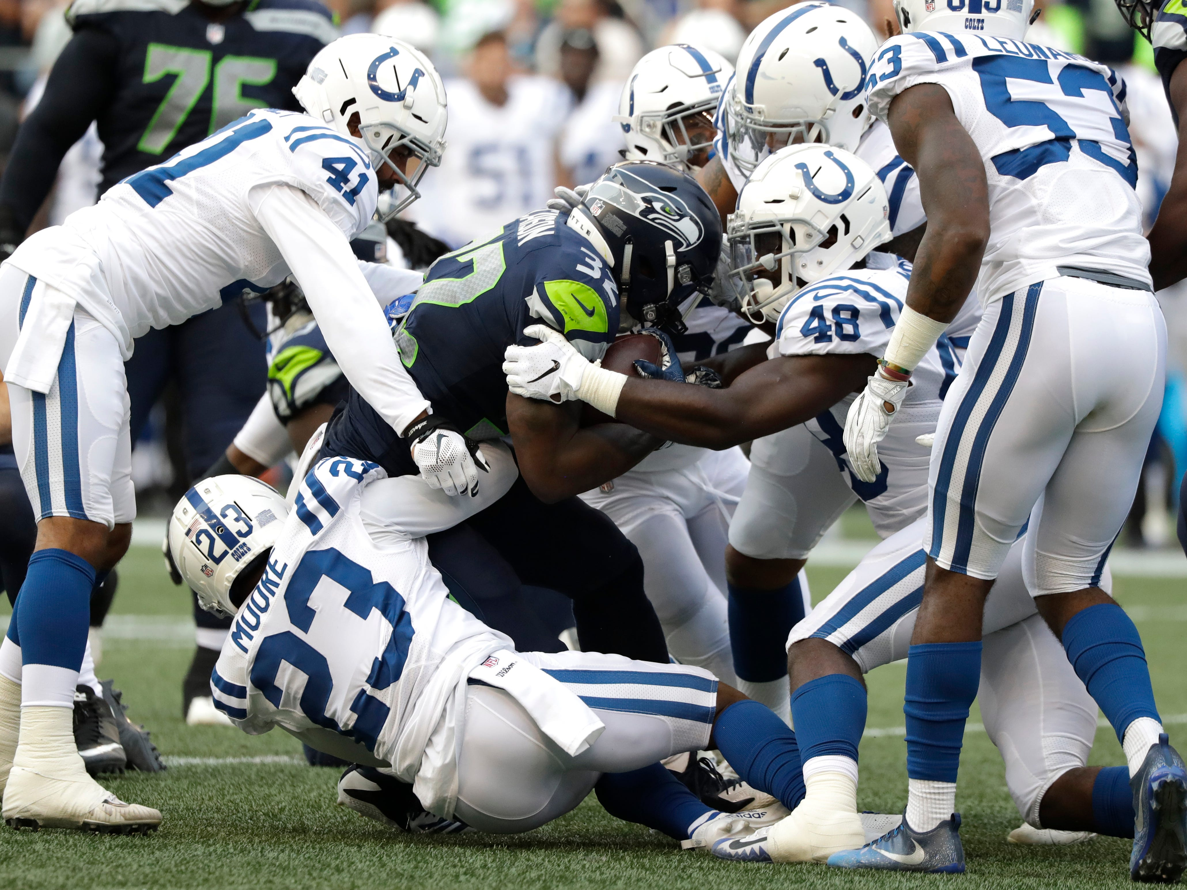 Seattle Seahawks running back Chris Carson (32) is tackled by Indianapolis Colts cornerback Kenny Moore (23) and linebacker Skai Moore (48) as he rushes during the first half of an NFL football preseason game, Thursday, Aug. 9, 2018, in Seattle. (AP Photo/Elaine Thompson)