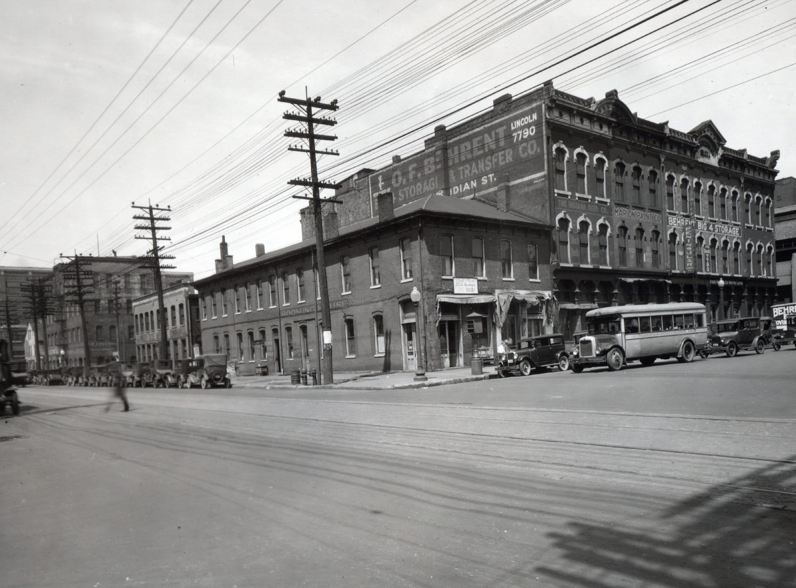 Intersection of Meridian and South looking northwest date unknown. The building at the corner is now the Slippery Noodle Inn.  The building was home to a rooming house and the front facing Meridian St. indicates it was Smith & Moon Ford Dealers sales and service. A barber shop is to the north.  The Behrent Storage & Transfer building also housed The Indiana Seed Co and Marion Paint Co. An Indianapolis Street Railway Co bus heads south on Meridian. The elevated railroad is to the right. Along South Street behind the rooming house is South Side Welding Company