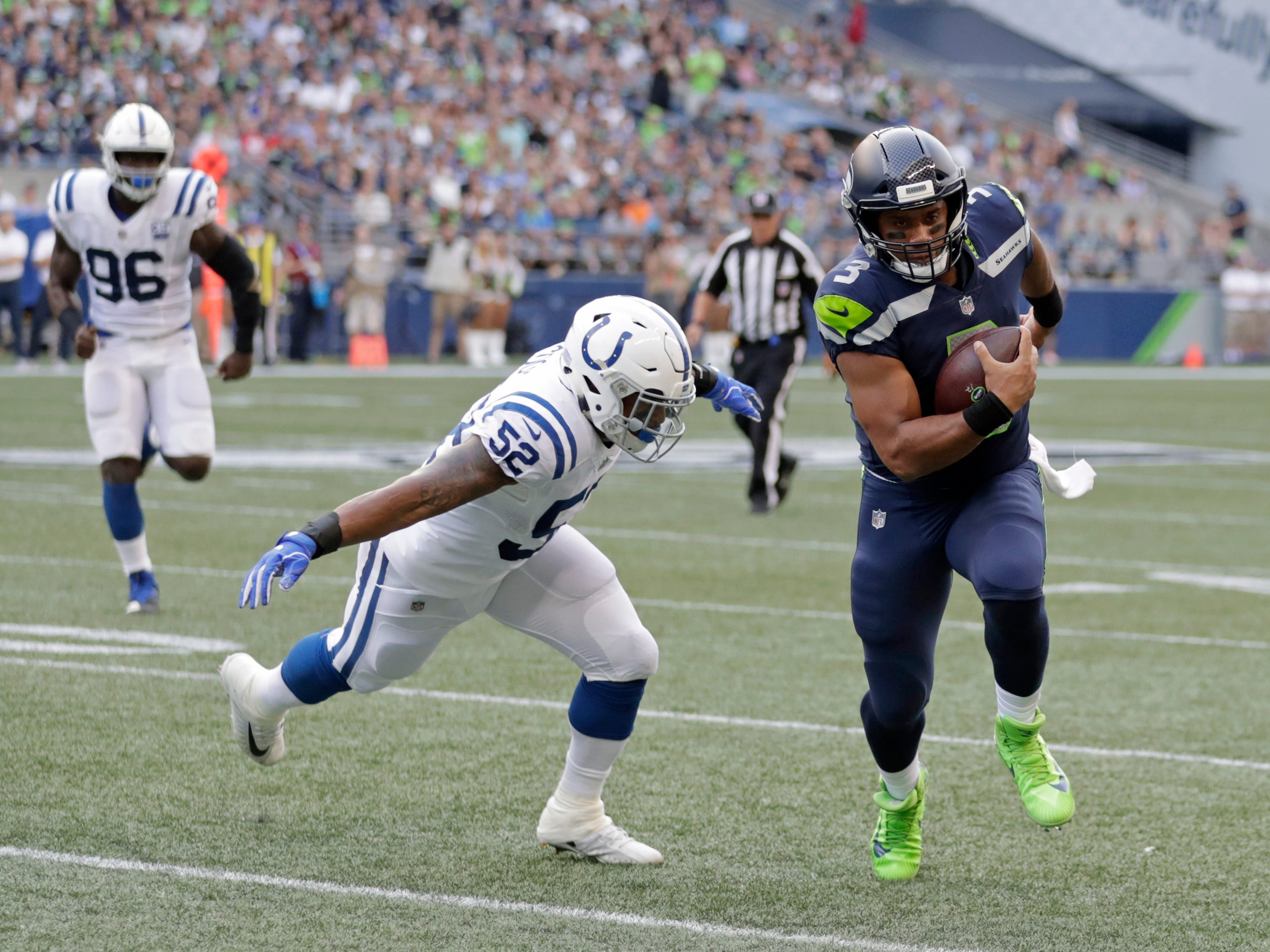 Seattle Seahawks quarterback Russell Wilson, right, scrambles with the ball as Indianapolis Colts linebacker Najee Goode (52) closes in during the first half of an NFL football preseason game, Thursday, Aug. 9, 2018, in Seattle.