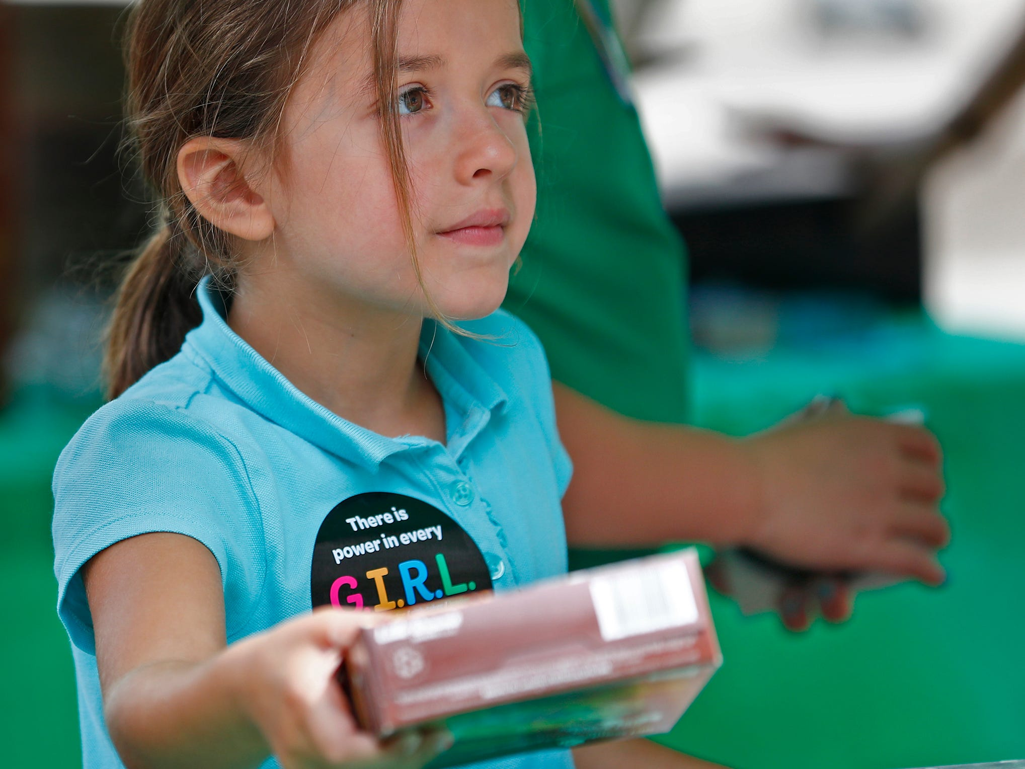 Jordan Morales hands out boxes of Girl Scouts S'mores cookies during the Girl Scouts' S'mores on the Circle event, Friday, Aug. 10, 2018.  The event celebrated National S'mores Day.  Seven local chefs were featured, creating gourmet s'mores treats, sold as a fundraiser.  Proceeds go for financial assistance for Girl Scouts, helping all girls who want to be a girl scout participating in hands-on adventures and STEM activities.