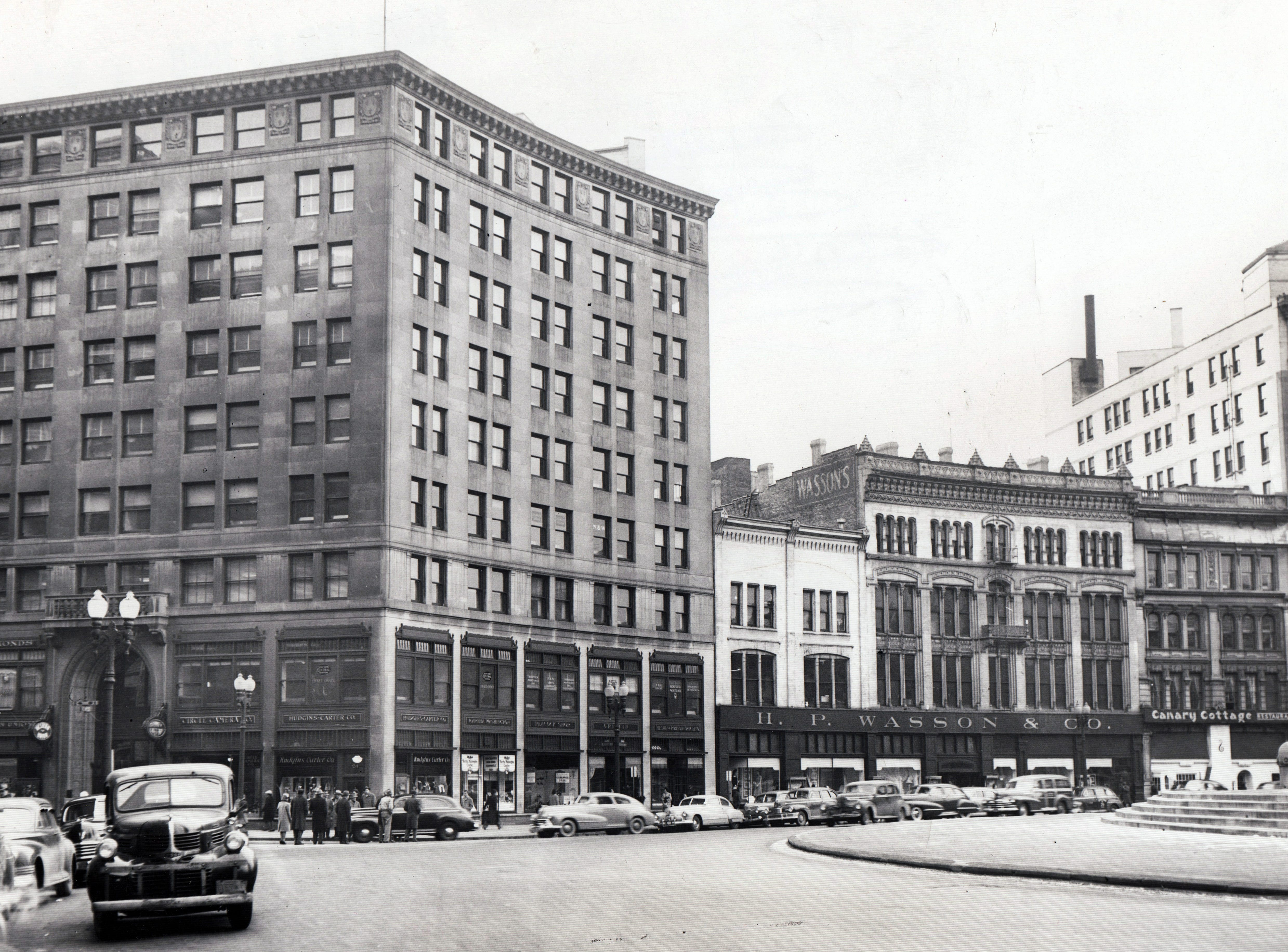 The southwest segment of Monument Circle, February 13, 1948. Businesses include the Circle Camera Co., the Hudgins Carter Co., the Peacock Shop, a New York Central Railroad ticket office on the second floor,  H.P. Wasson & Co., the Canary Cottage Restaurant.