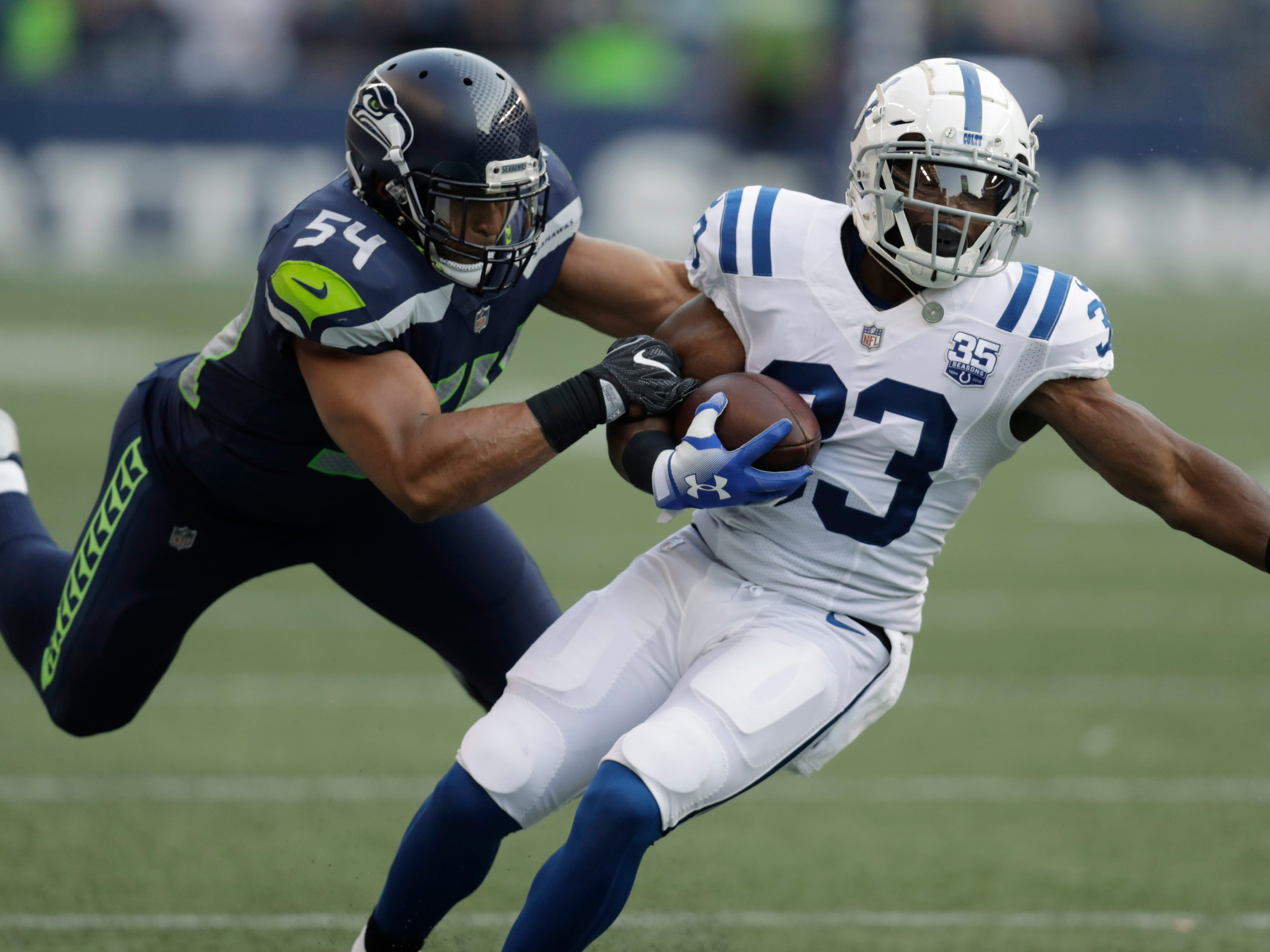 Seattle Seahawks linebacker Bobby Wagner (54) tackles Indianapolis Colts running back Robert Turbin (33) during the first half of an NFL football preseason game, Thursday, Aug. 9, 2018, in Seattle.