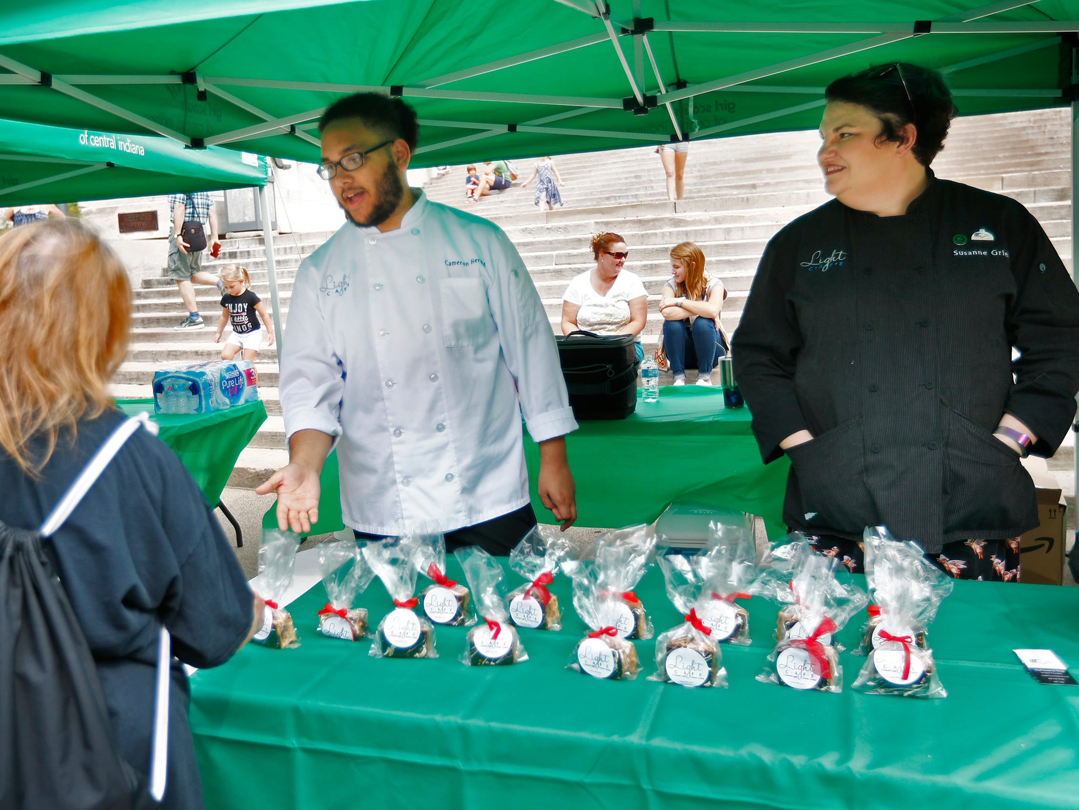 Cameron Herald, left, a student at J Everett Light Career Center, and Chef Susanne Grier hand out s'mores at their booth, during the Girl Scouts' S'mores on the Circle event, Friday, Aug. 10, 2018.  The event celebrated National S'mores Day.  Seven local chefs were featured, creating gourmet s'mores treats, sold as a fundraiser.  Proceeds go for financial assistance for Girl Scouts, helping all girls who want to be a girl scout participating in hands-on adventures and STEM activities.
