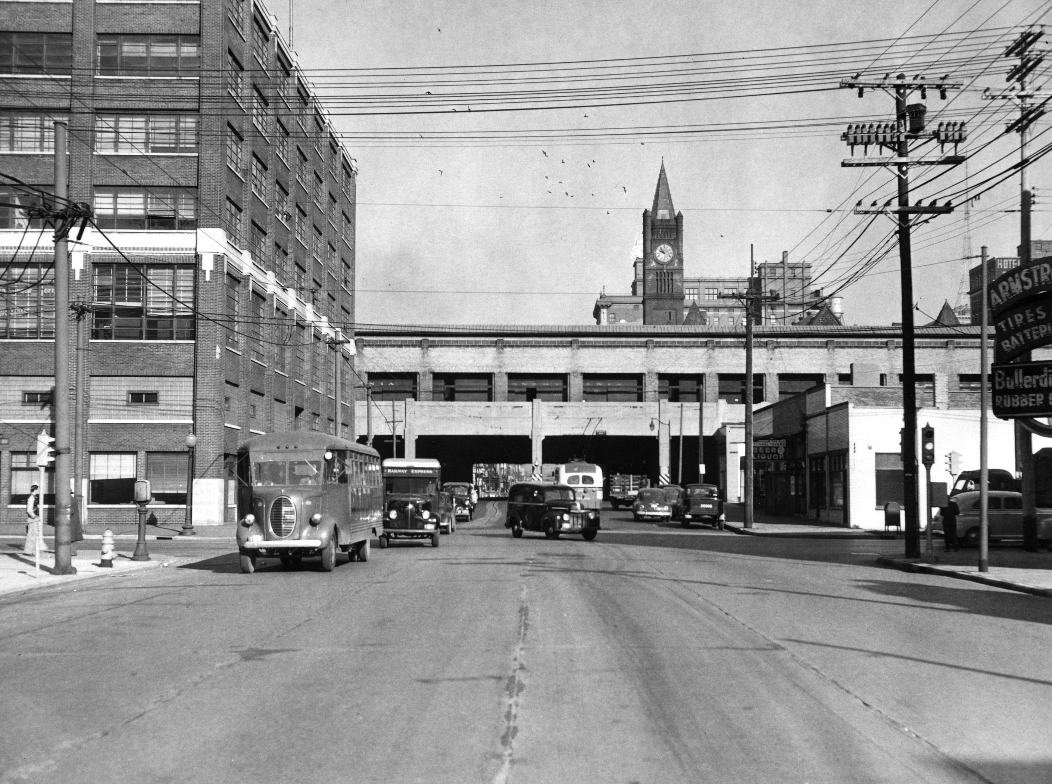 Illinois Street looking north near the intersection of South Street.  Armstrong Tires & Batteries at the far right. The railroad overpass - which you can actually see a train passing through is now covered over.  The building to the left is the Ilinois St. Post Office Station and is now where the Greyhound Bus and Amtrak terminal now stands.  Union Station clock is in the background.  November 22, 1949.