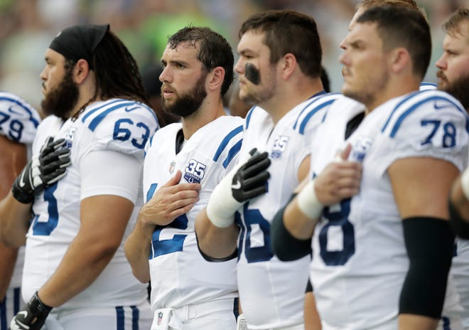 Indianapolis Colts players, including quarterback Andrew Luck, second from left, stand during the singing of the national anthem before an NFL football preseason game against the Seattle Seahawks, Thursday, Aug. 9, 2018, in Seattle.