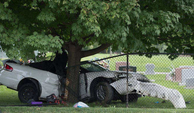 The scene of a fatal car crash into Concordia Cemetery just south of East Southern Avenue and South Meridian Street, that left at least one other person injured, Indianapolis, Friday, Aug. 10, 2018. An earlier police scanner report indicated the crash followed a police chase.