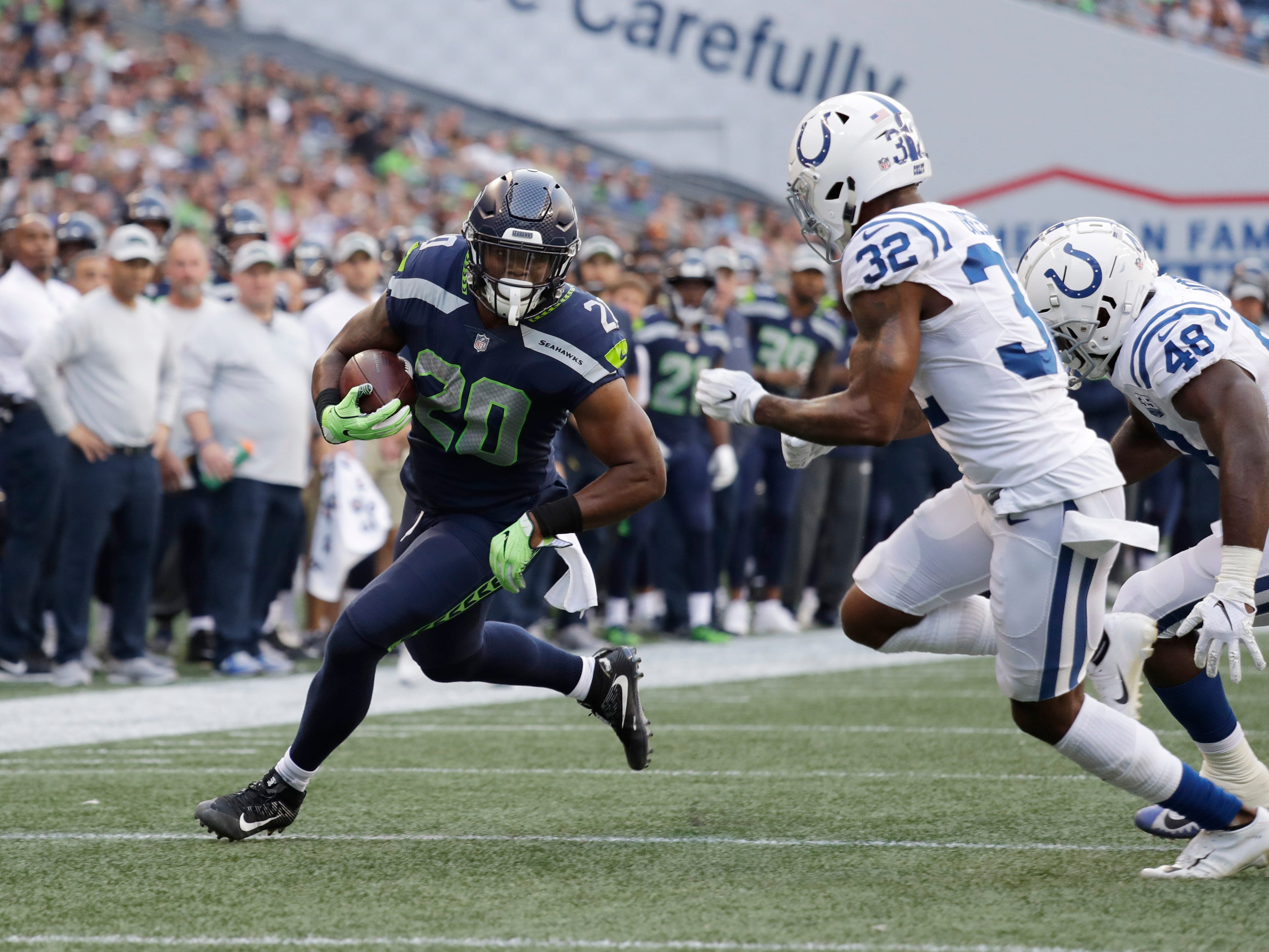 Seattle Seahawks running back Rashaad Penny (20) rushes past Indianapolis Colts defensive back T.J. Green (32) during the first half of an NFL football preseason game, Thursday, Aug. 9, 2018, in Seattle. (AP Photo/Elaine Thompson)