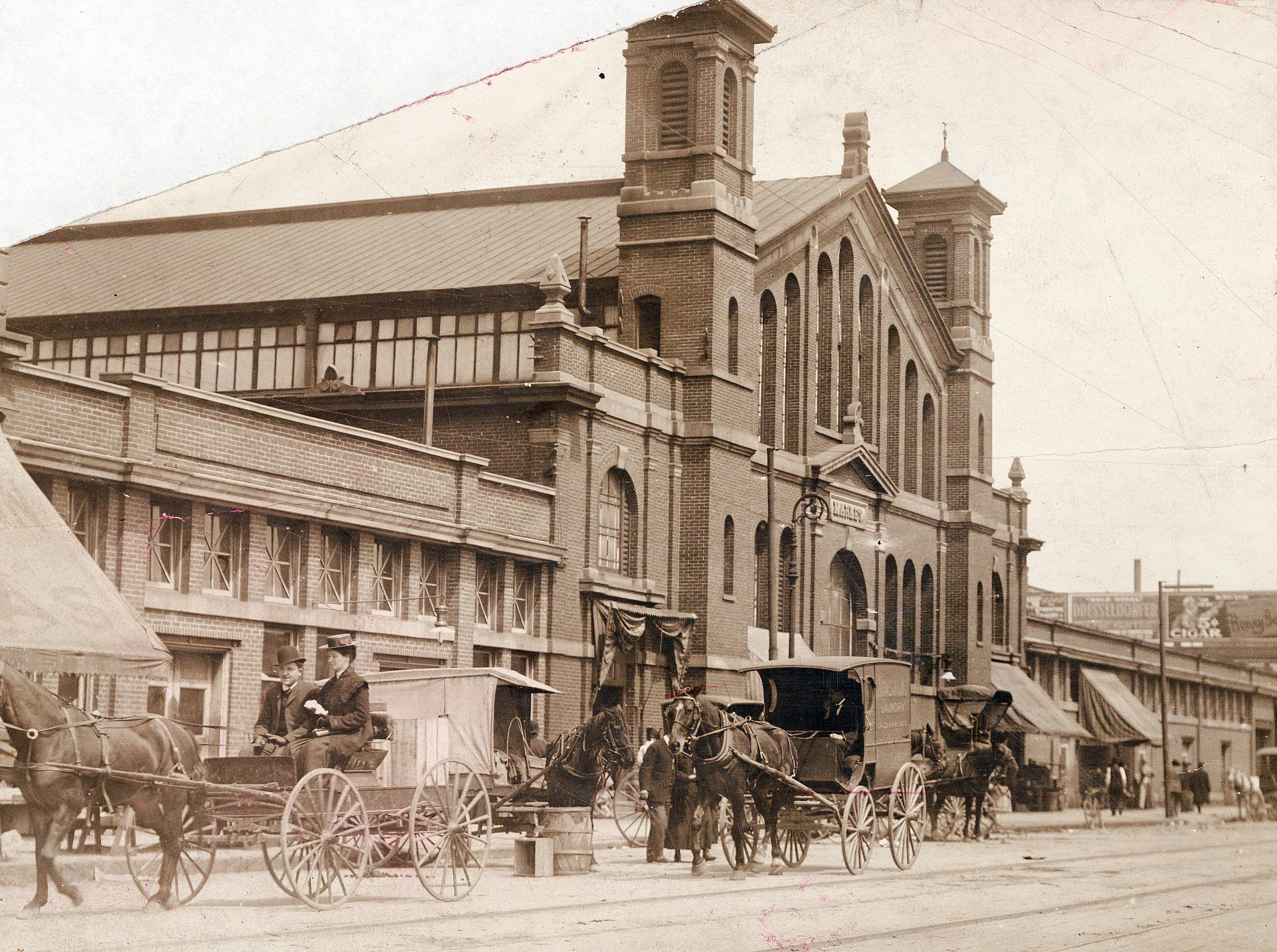 Horses and buggies ambled past the City Market in this view from 1908, looking northeast with Market Street in the foreground.  When sidewalk stands outside the building began to flourish, merchants in the City Market complained the curb merchants were taking away their business. Subsequently, the outside stands were abolished.