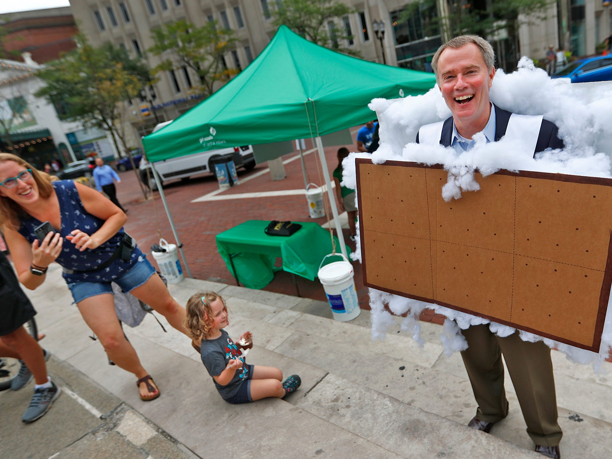 Mayor Joe Hogsett supports Girl Scouts by putting on a s'mores outfit during the Girl Scouts' S'mores on the Circle event, Friday, Aug. 10, 2018.  He came to the event to get a treat and to make a proclamation, naming the day Girl Scout S'mores on the Circle Day.  The event celebrated National S'mores Day.  Seven local chefs were featured, creating gourmet s'mores treats, sold as a fundraiser.  Proceeds go for financial assistance for Girl Scouts, helping all girls who want to be a girl scout participating in hands-on adventures and STEM activities.