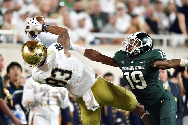 Notre Dame wide receiver Chase Claypool (83) caught a pass as Michigan State Spartans cornerback Josh Butler (19) defended in a game last year at Spartan Stadium. Mandatory Credit: Matt Cashore/USA TODAY Sports