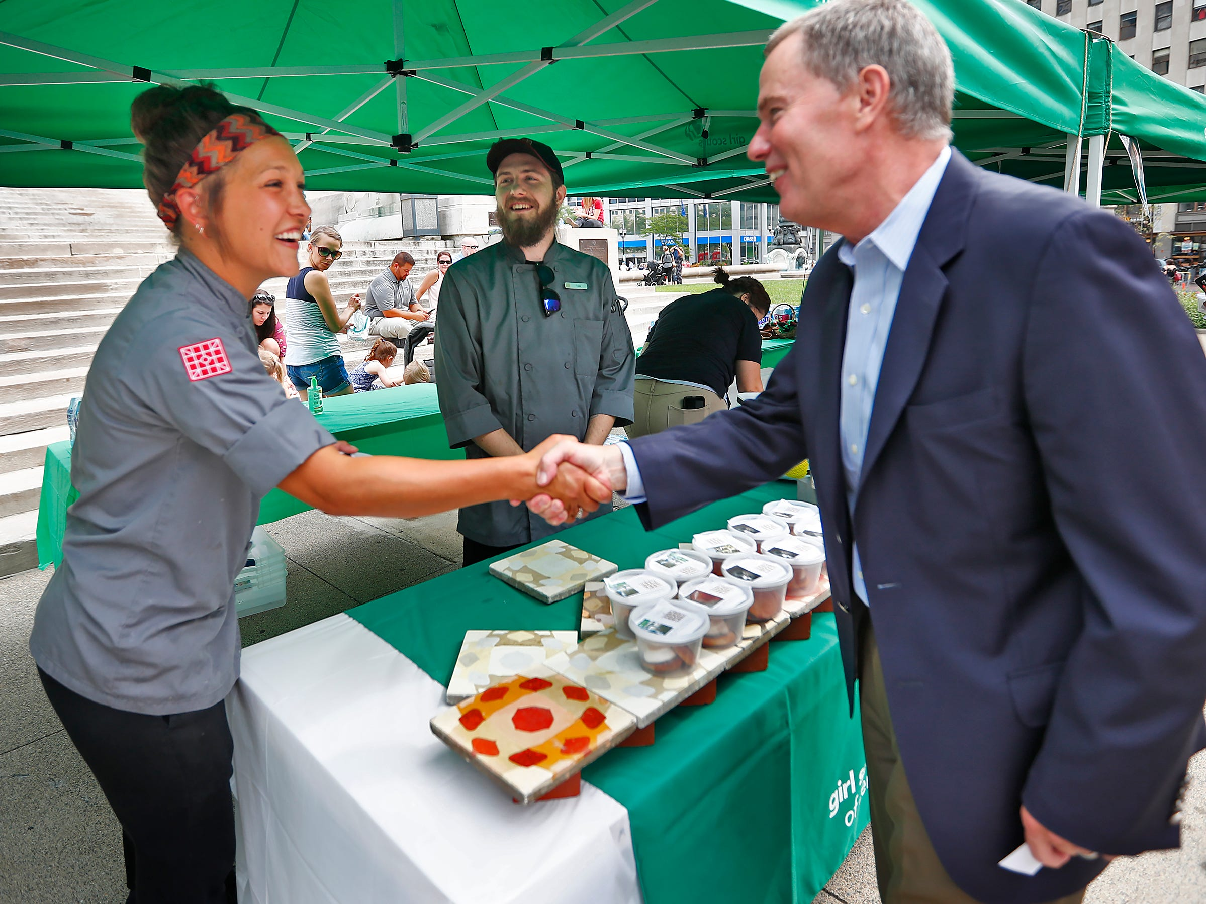 Chef Erica Oakley, from The Alexander, meets Mayor Joe Hogsett, during the Girl Scouts' S'mores on the Circle event, Friday, Aug. 10, 2018.  The event celebrated National S'mores Day.  Seven local chefs, including Oakley, were featured, creating gourmet s'mores treats, sold as a fundraiser.  Proceeds go for financial assistance for Girl Scouts, helping all girls who want to be a girl scout participating in hands-on adventures and STEM activities.