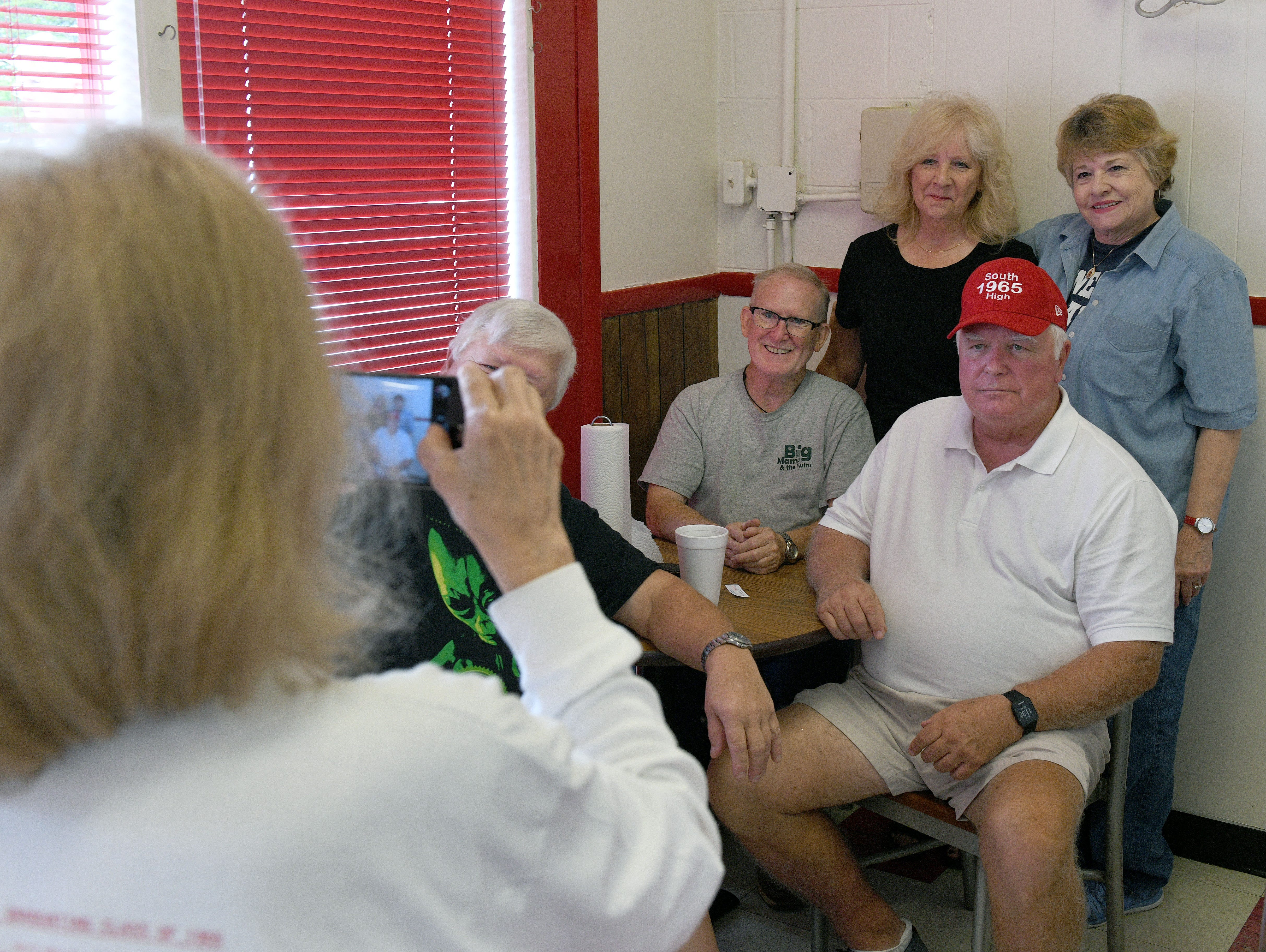 Members of the South High School Class of 1965 get a photo made as they gathered at the newly opened Scotts, in the old Kay's Ice Cream building,  Friday, August 10, 2018.