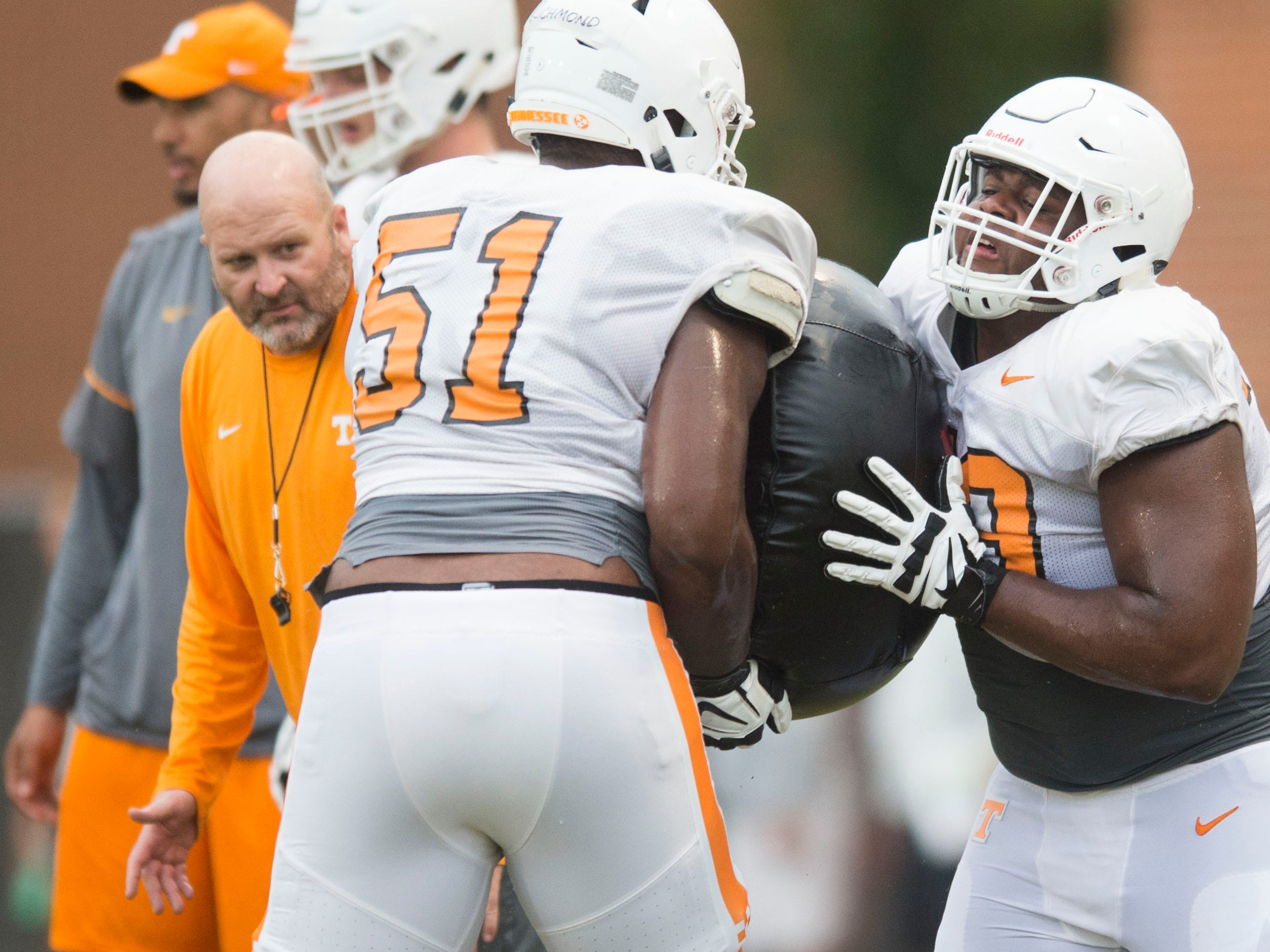 Tennessee offensive line coach Will Friend watch offensive linemen Drew Richmond, left, and Jarious Abercrombie drill during football practice at Haslam Field on Thursday, August 9, 2018.
