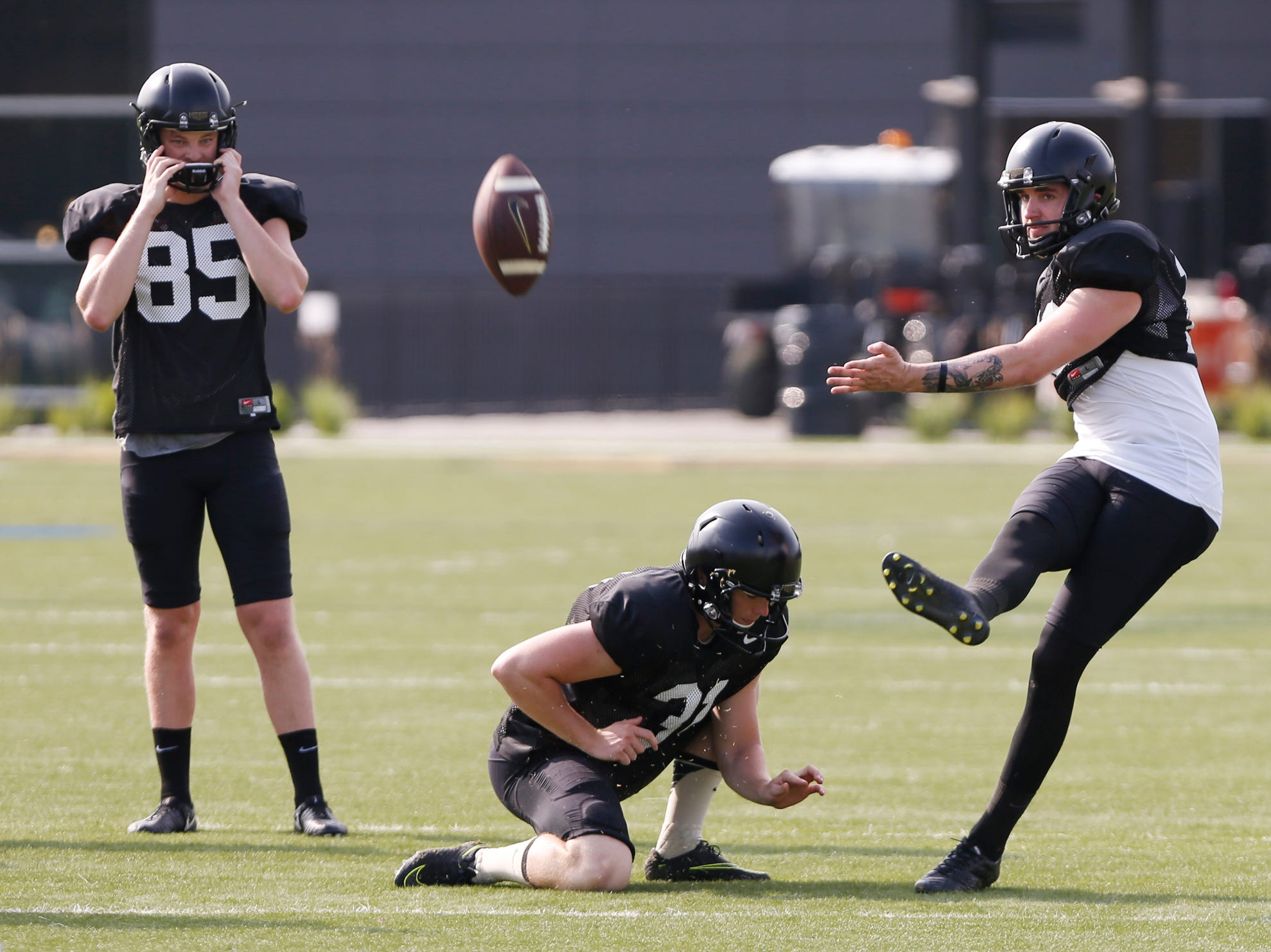 Kicker Spencer Evans with a field goal attempt with punter Joe Schopper as fellow kicker J.D. Dellinger looks on during Purdue football practice Friday, August 10, 2018, in West Lafayette.