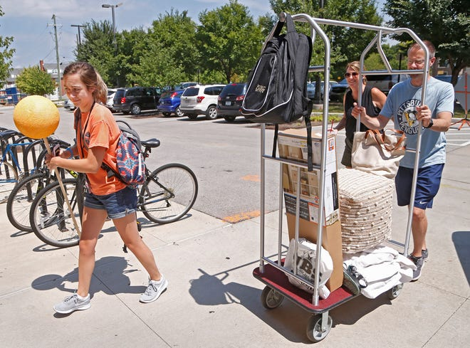 With her unfinished beacon in hand, Allyson Prichard gets help from her parents, Jeff and Donna Prichard, as she moves her belongings into Third Street Suites Friday, August 10, 2018, on the campus of Purdue University. Prichard, a sophomore, is a team leader for Boiler Gold Rush. The beacon helps new students in Boiler Gold Rush to quickly locate their team leader.