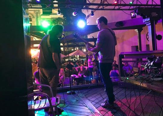 David Paul, left, and Mitch Barker perform Thursday, Aug. 9, on the patio at Digby's in downtown Lafayette at an open mic night dedicated to Eric Peacock, a guitarist who was killed Aug. 1 in a hit-and-run crash on U.S. 52.