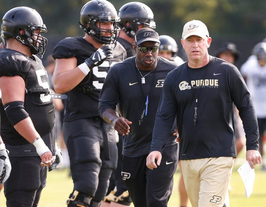 Head coach Jeff Brohm, right, and wide receivers coach and co-offensive coordinator JaMarcus Shephard get set to scrimmage the offense and defense during Purdue football practice Friday, August 10, 2018, in West Lafayette.