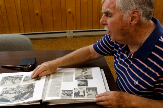 Jack Weidner looks through a scrapbook his wife created of photographs and newspaper clippings from his 34 years as mayor of Pleasantville. Weidner retired from office in June.