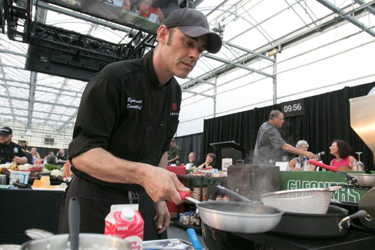 Chef Ryan Louwaert from Bourbons heats a sauce in the Gleaners Iron Chef Competition benefiting Gleaners Community Food Bank of Southeastern Michigan, held at Bordine's Nursery Thursday, Aug. 9, 2018.