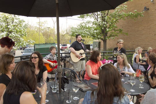 A crowd enjoy the music of the band Hidden Highways Thursday, May 7, 2015 on the patio of the Downtown Main Martini Bar & Grille during Ladies' Night Out. The business will close after Sunday.