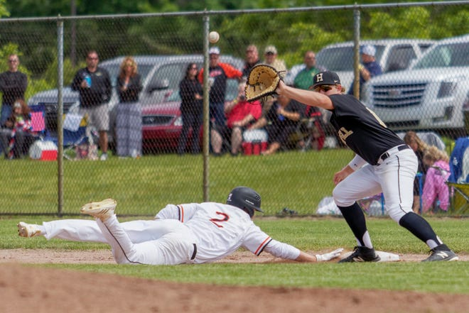 Brighton's Jack Krause dives back into first base during the 2018 district championship game against Howell.