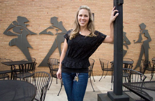 Lindsay Palizzi, shown Thursday, May 9, 2013, co-owns the Downtown Main and Martini Bar with her husband Nick. The business closed after 11 years in downtown Brighton. Six silhouette statues on the outside wall by the patio will be included in an upcoming auction.