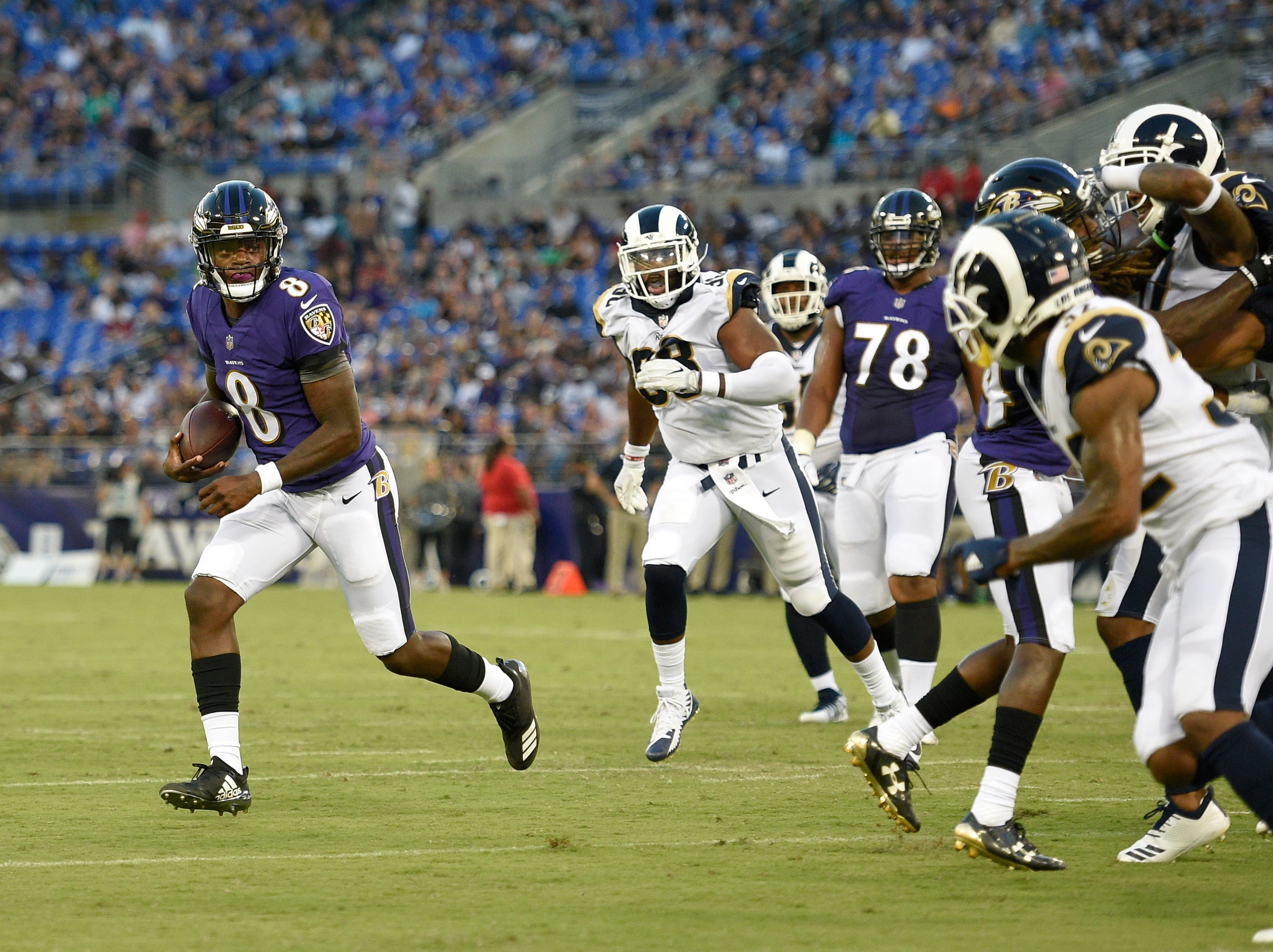 Baltimore Ravens quarterback Lamar Jackson, left, rushes for a touchdown in the first half of a preseason NFL football game against the Los Angeles Rams, Thursday, Aug. 9, 2018, in Baltimore. (AP Photo/Nick Wass)