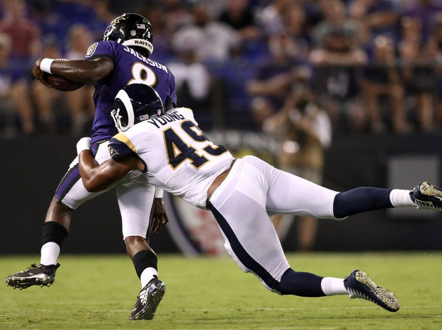BALTIMORE, MD - AUGUST 09: Lamar Jackson #8 of the Baltimore Ravens rushes past Trevon Young #49 of the Los Angeles Rams in the first half during a preseason game at M&T Bank Stadium on August 9, 2018 in Baltimore, Maryland. (Photo by Patrick Smith/Getty Images)