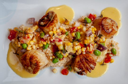 Diver scallops over tasso ham grits with southern succotash and smoked corn butter sauce prepared by chef John Varanese at River House.