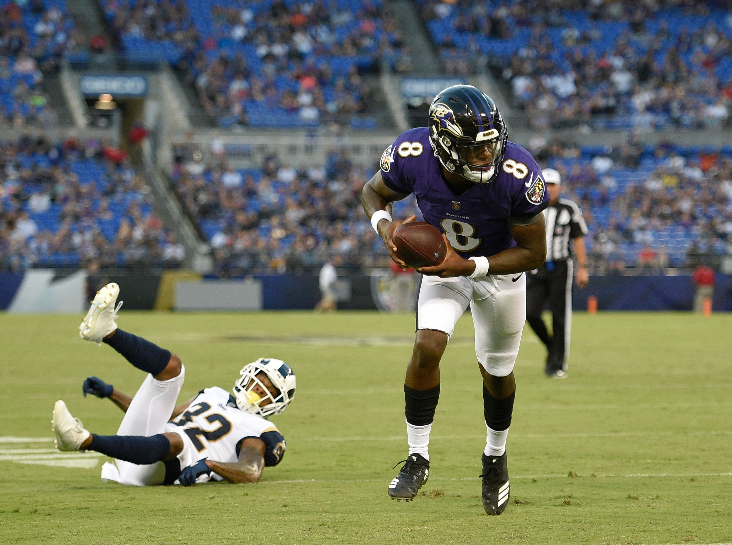 Baltimore Ravens quarterback Lamar Jackson, right, rushes past Los Angeles Rams cornerback Troy Hill for a touchdown in the first half of a preseason NFL football game, Thursday, Aug. 9, 2018, in Baltimore. (AP Photo/Nick Wass)