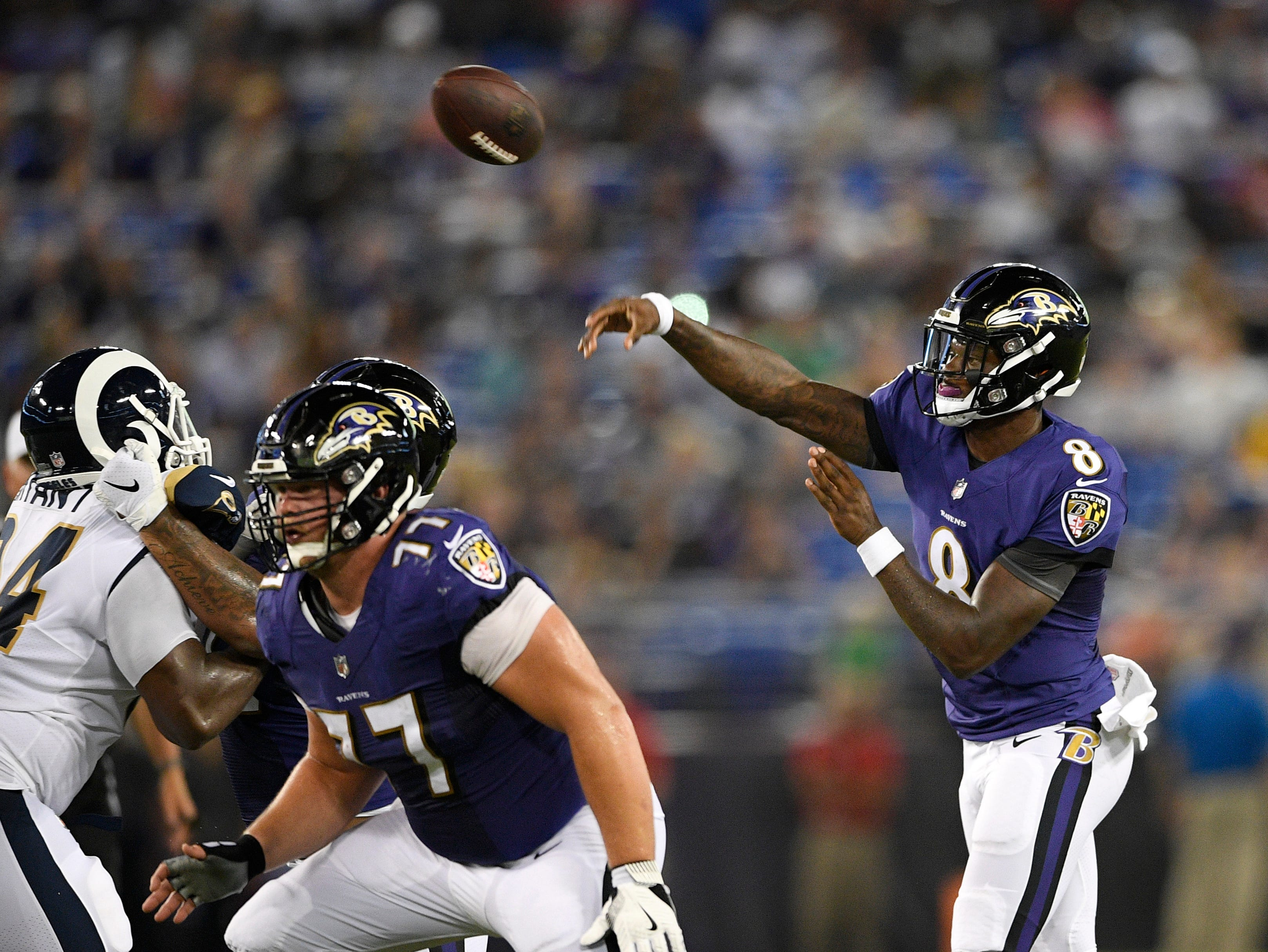 Baltimore Ravens quarterback Lamar Jackson, right, throws to a receiver in the first half of a preseason NFL football game against the Los Angeles Rams, Thursday, Aug. 9, 2018, in Baltimore. (AP Photo/Nick Wass)