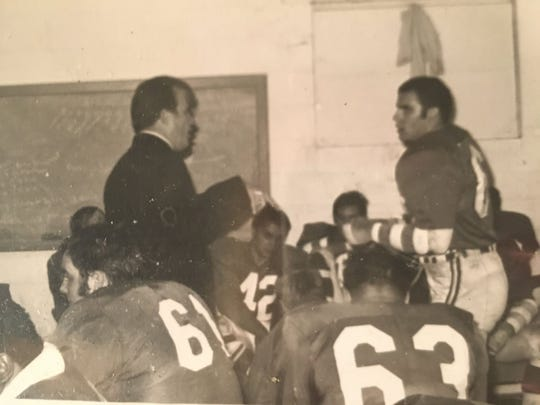 """Lansing All-Stars head coach Robert """"Turf"""" Kauffman and former MSU All-American tackle Jerry West talk  with one another in the Lansing All-Star locker room. The All-Stars won minor league championships from 1969-1971, including a 28-0 stretch in 1969 and 1970."""