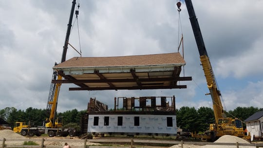 The roof of the historic Meeme House Inn is re-set and secured on the structure Aug. 3.