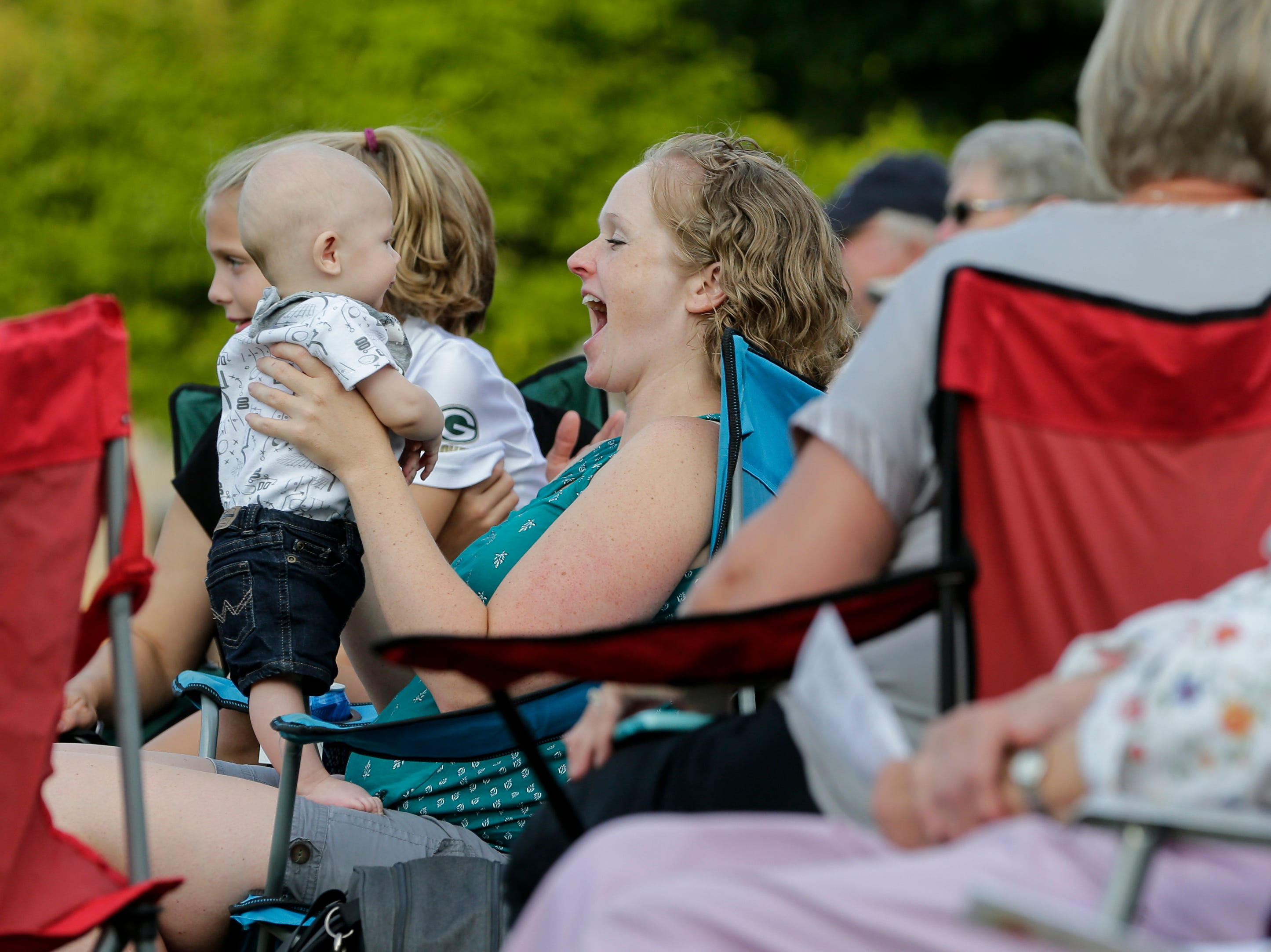 McKensie Vogel smiles at her little boy Easton, 1, as the Two Rivers Community Band plays their final concert of the season at Central Park Thursday, August 9, 2018, in Two Rivers, Wis. Josh Clark/USA TODAY NETWORK-Wisconsin