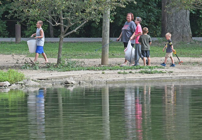 Brothers Ryker Cullen, 4, Logan Cullen, 6, and Kaden Lapene, 8, and their cousin Spencer Canankamp, 12, collect trash with Sandy Eulett, the three boys'grandmother and aunt of Spencer on Friday at North Lake Park.