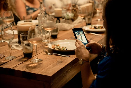 A guest takes a photo of her dish at a recent Taste of Gallery pop-up dinner.