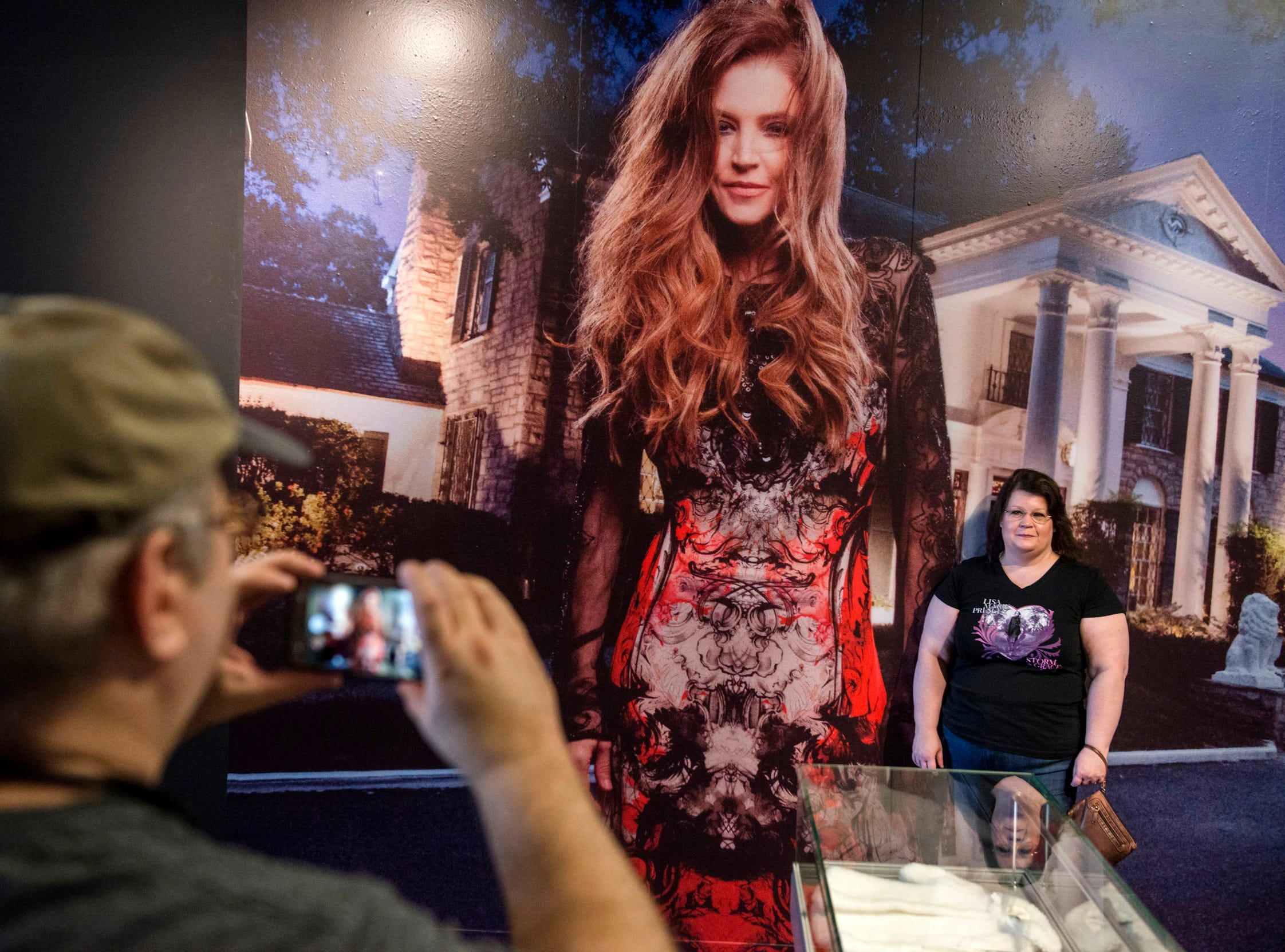 "August 10, 2018 - Columbus, Ohio resdient Billy Eanes takes a photo of Stacy Eanes during a private ribbon-cutting event for the new exhibit ""Lisa Marie: Growing Up Presley"" at Elvis Presley's Memphis entertainment complex."