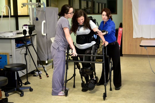 August 9, 2018 - Hillary Barrera (center) demonstrates the EksoGT robotic exoskeleton at Baptist Memorial Rehabilitation Hospital on Thursday evening. Barrera is able to stand and walk with assistance from the device and physical therapists Kali Potts (left) and Leslie VanHiel.