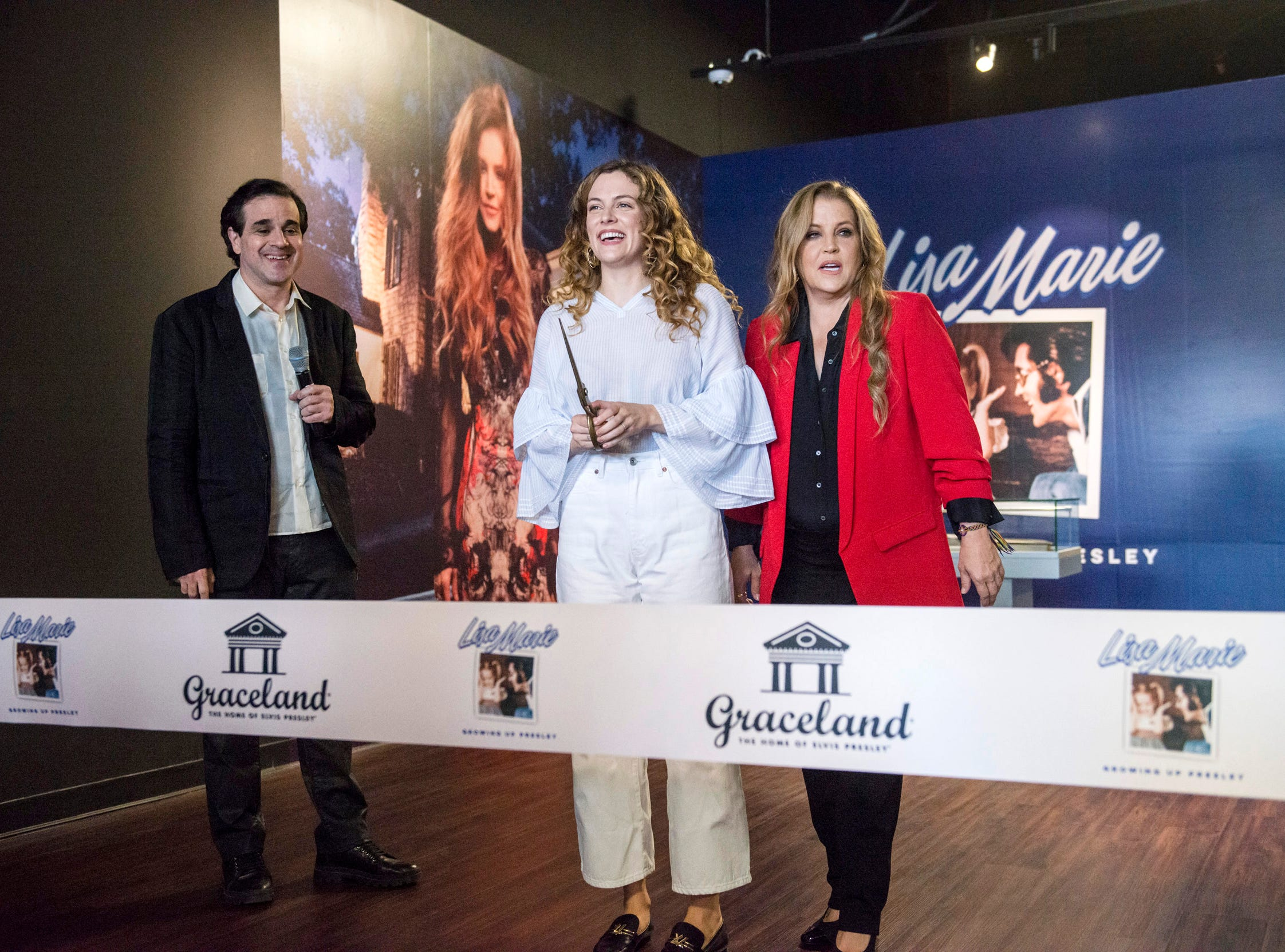 "August 10, 2018 - Lisa Marie Presley, right, and her daughter Riley Keough, center, along with Elvis Presley Enterprises principal Joel Weinshanker, left, participate in a private ribbon-cutting event for the new exhibit ""Lisa Marie: Growing Up Presley"" at Elvis Presley's Memphis entertainment complex."
