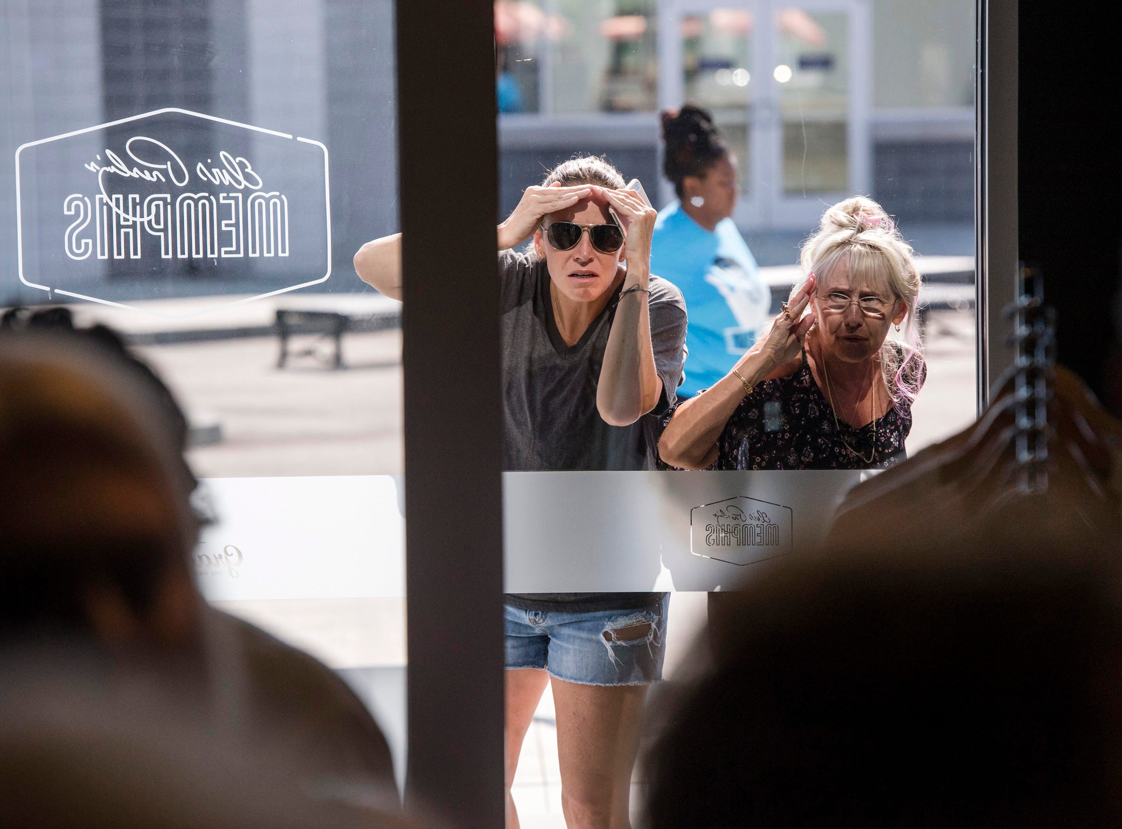 "August 10, 2018 - Women look through a window at a private ribbon-cutting event for the new exhibit ""Lisa Marie: Growing Up Presley"" at Elvis Presley's Memphis entertainment complex."